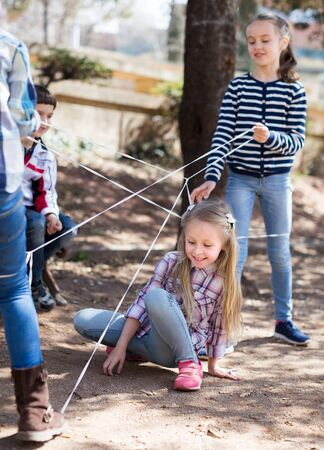 children games. smiling blonde Girl goes through the tangled rope Stock Photo