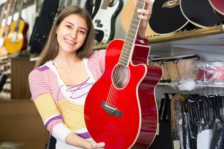 Young woman customer buying new guitar in store and smiling