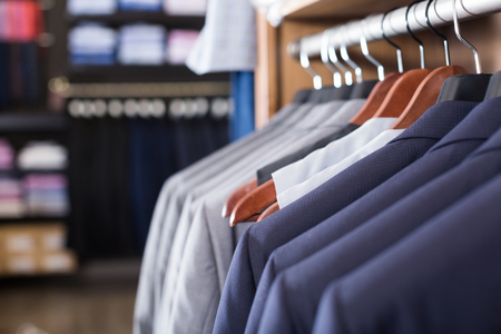 row of jackets on hangers in luxury men clothing store Stock Photo