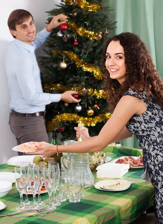 Young family decorating Christmas tree and serving  festive table in home