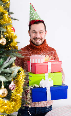 Portrait of Man on holiday in hat with gifts near Christmas tree