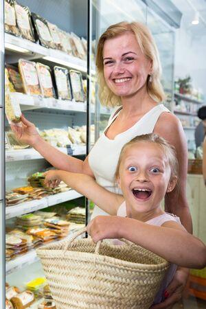 Jonge moeder met dochter kopen gekoeld voedsel in de supermarkt Stockfoto - 86699663
