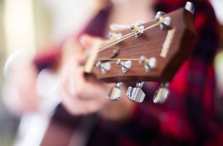 girl holding guitar in music shop. Focus on the head of guitar