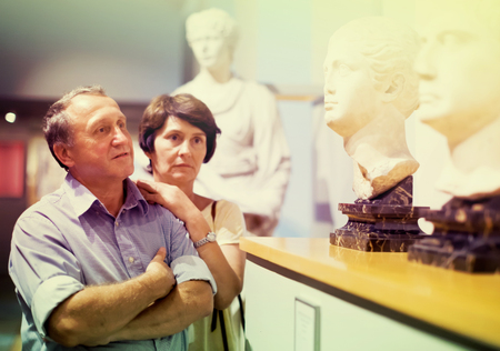 mature couple turists examines the exhibit in historical museum Stock Photo