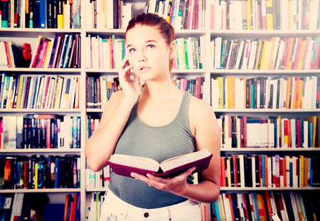 perplexed brunete girl chooses a book in the library