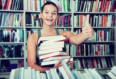 ordinary girl holding stack of books shows thump up in a bookstore