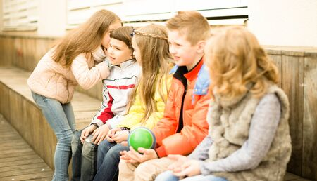 modern Children on a bench playing Chinese whispers Stock Photo