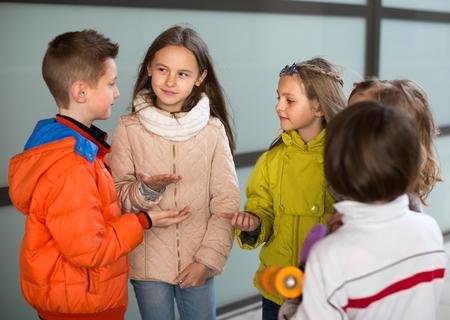 Retrato de los niños se comunican en el patio de la escuela en otoño