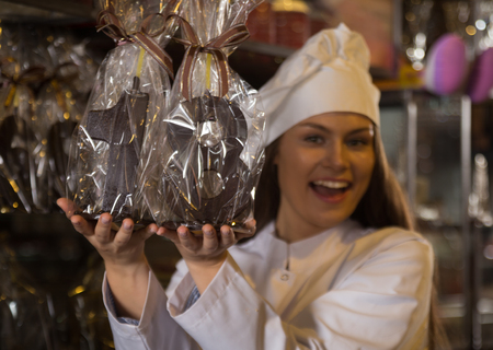 Portret of young shopgirl posing with fine chocolate numbers and cakes for sale