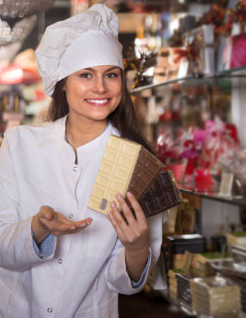 Young woman selling fine chocolates and confectionery in cafe