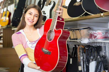 Girl customer buying red guitar in store and smiling