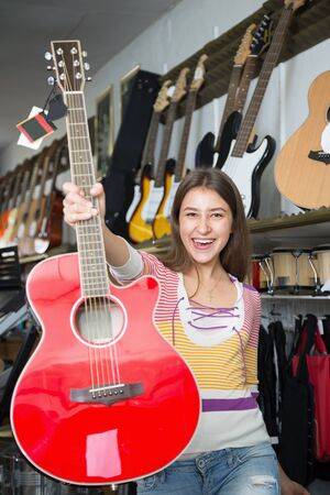 Guitarist girl buying new guitar in store and smiling Stock Photo