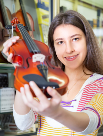 Pretty female customer purchasing violins in store and smiling