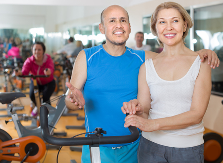 elderly latinos man and european woman in background bikes at the gym. focus on woman Stock Photo