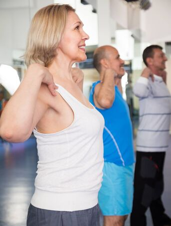 elderly blonde female and male exercise in modern gym