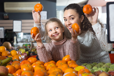 smiling  woman and happy blonde little girl posing whith mandarin in department fruits of store