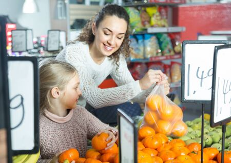 positive woman and little blonde girl posing whith mandarin in department fruits of store. focus on girl