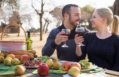 Portrait of young couple drinking wine at table in nature