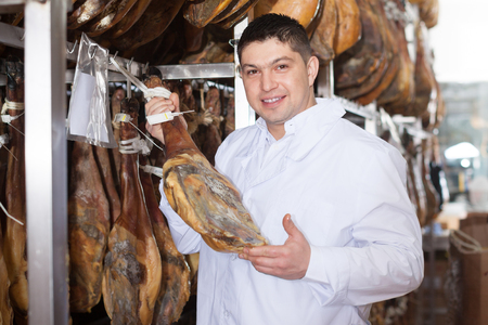 smiling worker in white gown checking joints of iberico jamon