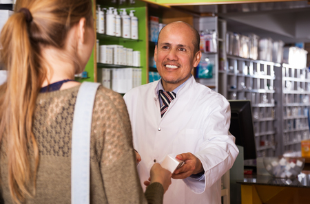 Girl near counter in pharmacy consulting with pharmacist Stock Photo