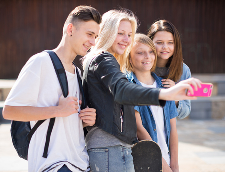 group of teenagers taking pictures of themselves on smartphone