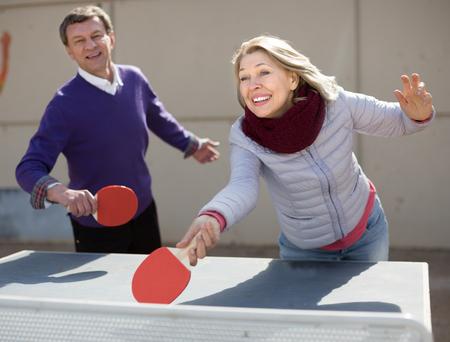 Uomo anziano attivo e una donna che giocano a ping-pong Archivio Fotografico - 94158306