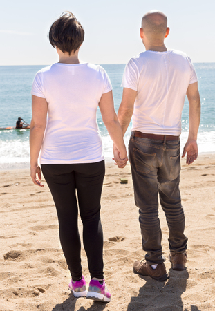 Mature couple embracing looking at the sea on the beach in summer on a sunny day Stock Photo