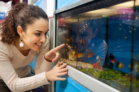 Portret van vrolijk meisje die tropische vissen in petshop kiezen