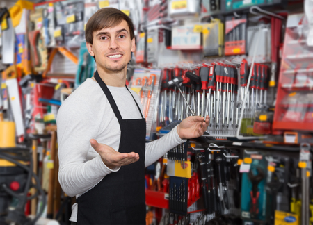 amiable young salesman in apron with tools in supermarket