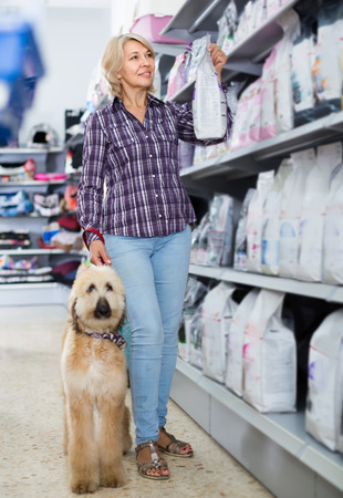 ordinary woman buying pet food for Afghan Shepherd puppy in shop for animal Stock Photo