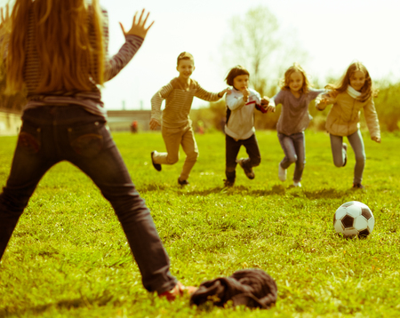 ordinary Children play with ball outdoors in spring. focus on ball