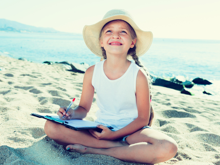 child girl in hat writes draws dreams with sand on seashore in summer