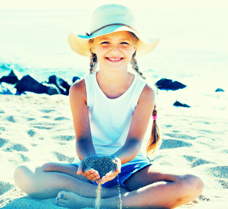 girl in hat playing with sand on sea coast in summer
