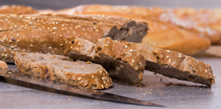 fresh slices of wheaten bread and knife on wooden surface