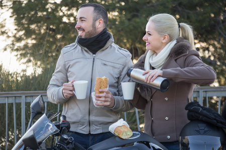 Portrait of pretty young adults drinking coffee and chatting near motorcycle