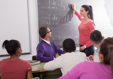 smiling cute student girl solves task near blackboard in classroom mathematics Banco de Imagens