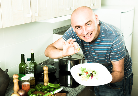 smiling man adds olives in fresh salad finally on home kitchen