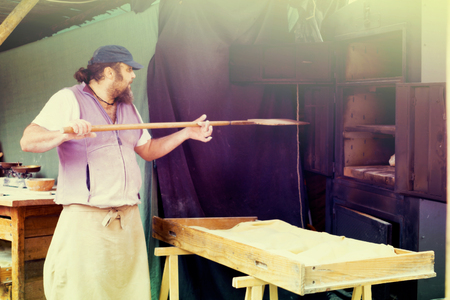 male baker puts bread on the shovel into the oven