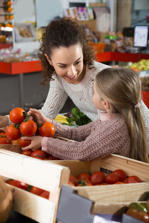 portret of young woman with beautiful daughter choosing tomatoes at store Stock Photo