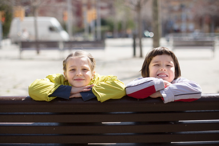 nice Boy with blonde girl sitting on bench outdoors in spring