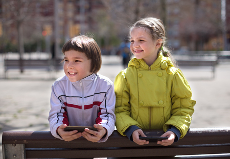 little boy with blonde girl on the bench with smartphones
