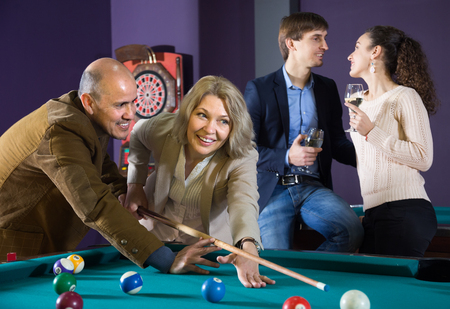 elderly couple learns to play billiards. young couple drinking wine. focus on mature woman
