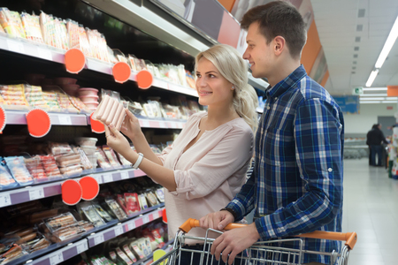 Young spouses purchasing in wurst section of shop