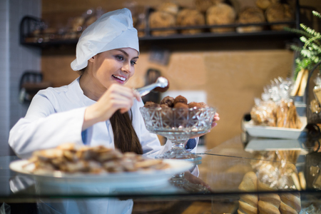 Smiling girl selling sweet pastry and tarts in coffee-house