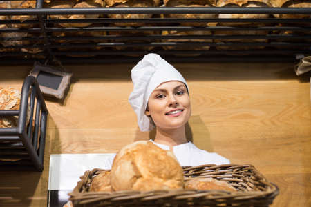 Young female staff selling fresh pastry and baguettes in local bakery
