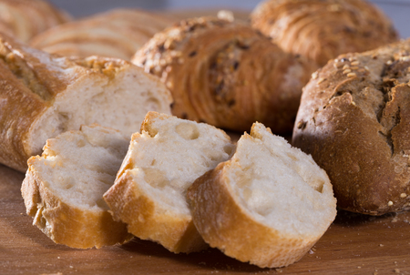 fresh slices of wheaten bread on wooden surface Stock Photo