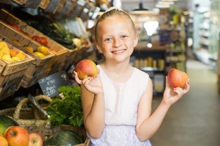 blonde girl choosing apples in vegetable shop. on labels of product names in Catalan