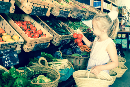 blonde girl choosing  tomatoes in vegetable shop. on labels of product names in Catalan Stock Photo