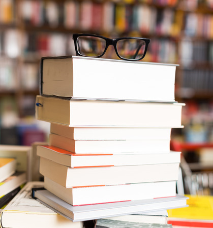 glasses on top of stack of art books lying on table in bookstore