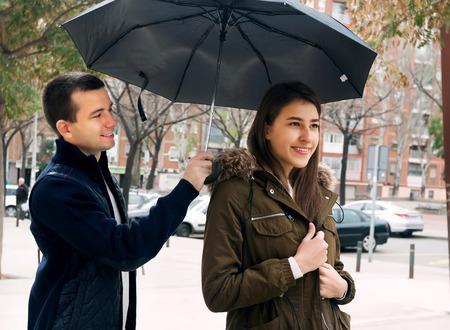 Happy young couple having a city walk and smiling in rain Archivio Fotografico